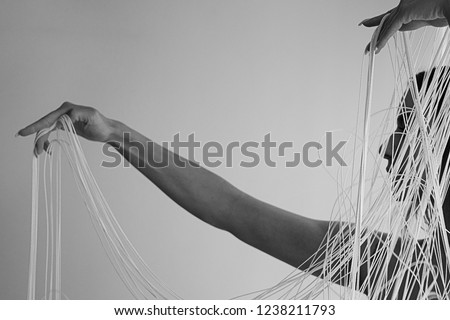black and white Image of the profile of a young attractive woman with uncovered shoulders decoratively pulling the white threads of a string curtain with hands, isolated, copy space, space for text