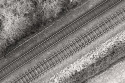 Black and white image of two railway tracks which consists of two parallel steel rails, anchored perpendicular to members called ties (sleepers) of concrete to maintain a consistent distance apart.