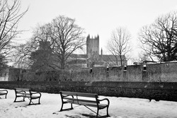 Black and white image of Wells cathedral wintery scene with Wells castle wall and moat to the front.  Snow covered pathway and empty benches outside in winter