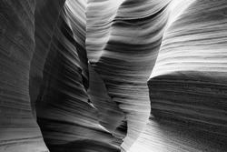 Black and white image through a slot canyon showing eroded textures and curving rock shapes