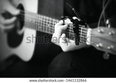 Black and white image, where a person plays a melody on an acoustic six-string guitar, on the fretboard of which the strings are clamped with a capo
