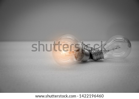 Black and white images of 3 bulbs with only 1 light bulb representing different ideas, good ideas and Success.