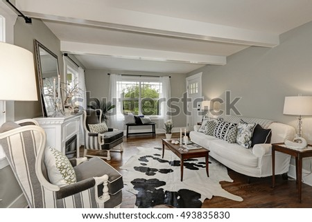 Black and white interior of luxury living room with wooden beams ceiling, cow hide on the floor and vintage furniture. Northwest, USA #493835830