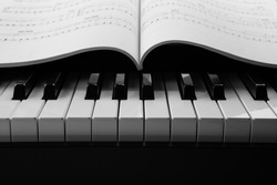 black and white keys of the piano closeup and musical book.