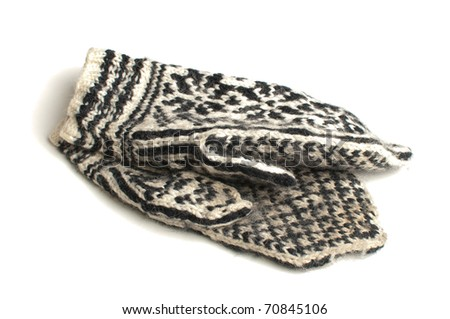 Black and white knitted mittens over white background
