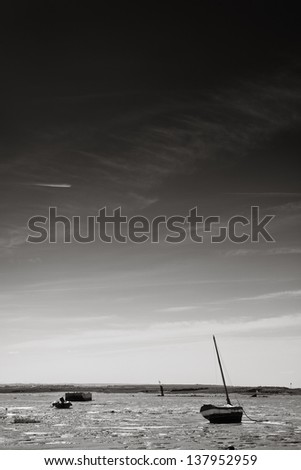 Black and white landscape image of Southend beach looking out at the boats on the mud when the sea is out, Essex, England