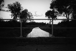 black and white landscape of river and some trees talen from old bridge. Clear sky with some clouds. Bright water. Bridge iron railing on foreground. Rectangles.