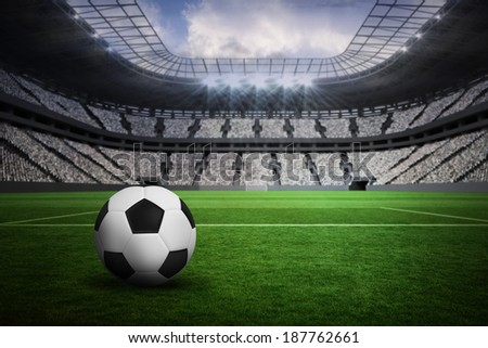 Black and white leather football in a vast football stadium with fans in white