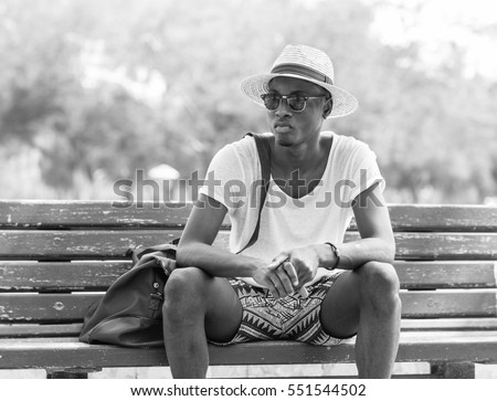Black and White lifestyle fashion portrait. Stylish young african man sitting alone on a park bench wearing sunglasses and wicker hat.   #551544502