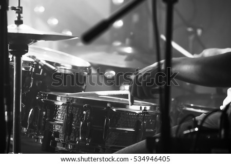 Black and white live music background, drummer plays with drumsticks on rock drum set. Closeup photo with soft selective focus