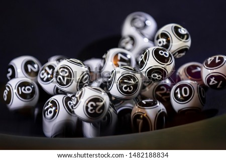 Black and white lottery balls in a bingo machine. Lottery balls in a sphere in motion. Gambling machine and euqipment. Number 13