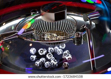 Black and white lottery balls in a rotating bingo machine. Lottery balls in a sphere in motion. Gambling machine and euqipment. Blurred lottery balls in a lotto machine. Number 16.