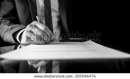 Black and white low angle image of the hand of a businessman in a suit signing a document or contract with a fountain pen on a reflective surface.
