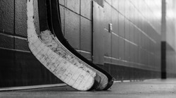 Black and white macro shot of hockey stick blades laid on a dirty arena floor - Shallow depth of field