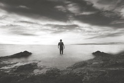 black and white man walking in the water in a wonderful sea