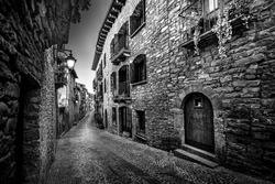 Black and white medieval old town street with stone houses and cobblestone floor, street lamps and dark and night atmosphere.
