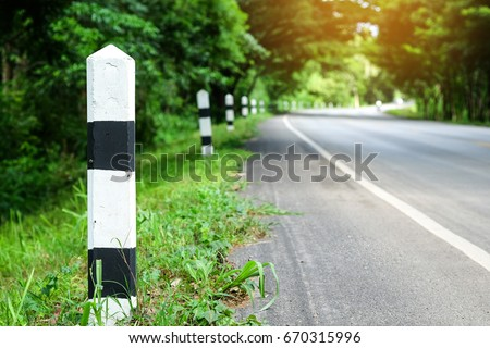 Black and white milestones with green grass roadside, Trees roadside in background . concept for next step.