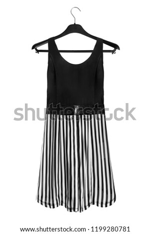 11b814c5046 Black and white mini dress with striped skirt on black clothes rack isolated  over white