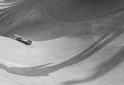 Black and white minimalist street photography shows shadow of person who lost his skateboard which is rolling away, against backdrop of curves of skate park.