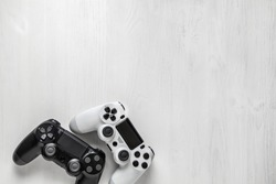 black and white modern gamepad on white wooden background