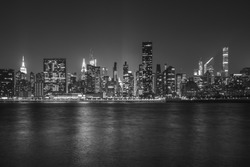 Black and White Monochromatic image of New York City Cityscape during Night Time with busy skyline and dense skyscrapers filling up the sky