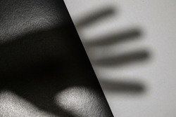 black and white monochrome paper background with human hand shadow on surface