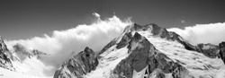 Black and white mountain panorama in clouds. Caucasus, region Dombay. View from the ski slope.