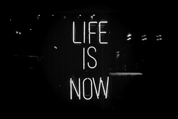 Black and white neon sign life is now. Glow quote about live and self motivation. Here and now abstract concept.