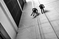 Black and white , Noise , Grain : Two People rappel wall to Repair , fix , filling crack Outdoor Concrete and cement wall building surface broken down
