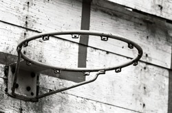 Black and white of old outdoor basketball hoop and backboard in school