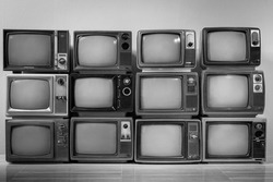 Black and white of old vintage televisions pile in the room. TVs wall