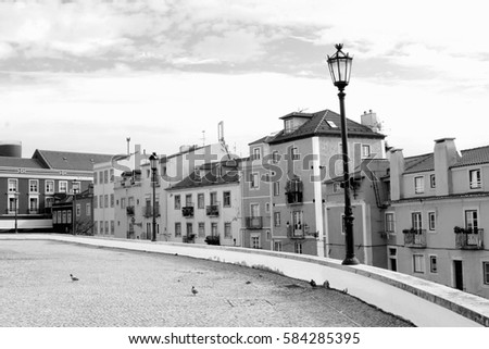 Black and white old town street with vintage  houses in historical Alfama, the oldest district of Lisbon, Portugal