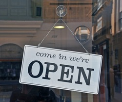 Black and white open sign hanging on the door
