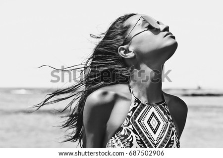Black and white outdoor fashion photo of beautiful happy woman at sea. Beach travel. Summer vibes