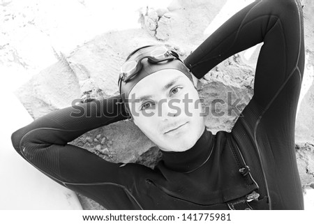 Black and white over head portrait view of a young surfer man relaxing on a white sand beach with a surfing board, wearing professional neoprene, goggles and rubber hat, aspirational lifestyle.