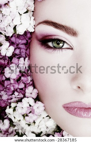 Black and white painted close-up portrait of girl with stylish makeup and flowers around her face