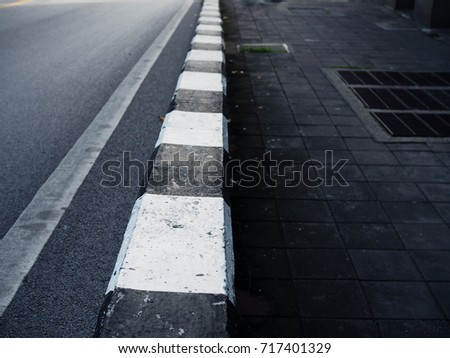 Black and white paved road border, with dark stone cement tile footpath floor and water drainage sewage iron mesh cover, depth extending, perspective