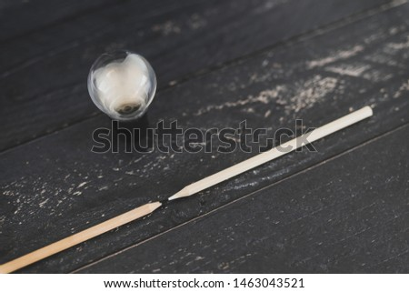 black and white pencils facing each other with light bulb next to them, concept of opposite ideas or contrasting opinions