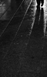 Black and white photo. City lights reflection in asphalt surface with alone (lonely) person silhouette. Rainy paving slab (road). Rain today in our town.