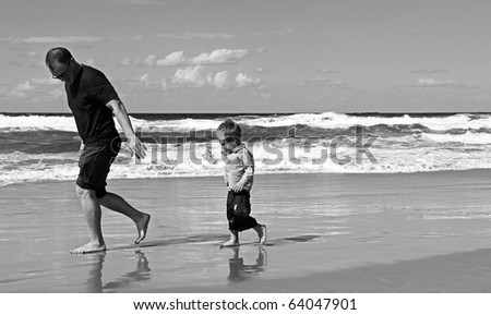 Black and white photo. Father playing with his son at beach