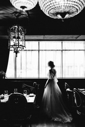black and white photo in vogue style delicious luxurious bride in a lush long expensive dress stands with her back at the window in a beautiful interior restaurant with chic chandeliers