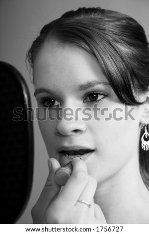 Black and white photo of a beautiful young woman applying lipstick.