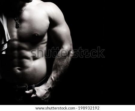 black and white photo of a bodybuilder man torso  on black background