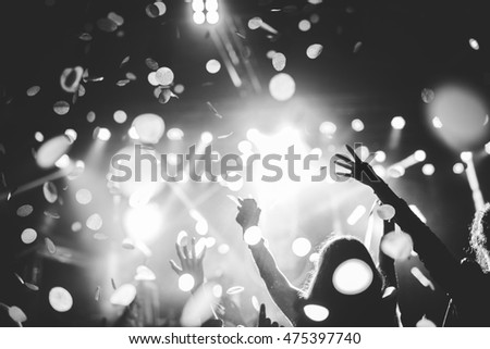 Black and white photo of a festival crowd rising their hands.