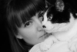 Black and white photo of a girl with a black and white cat on her shoulder.