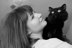 Black and white photo of a girl with a black cat on her shoulder.
