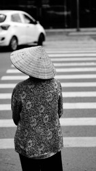 Black and white photo of a lonely woman with traditional asian hat walking in the streets of Ho Chi Min city, Vietnam.
