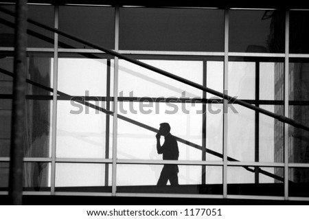 Black and white photo of a man talking on a cell phone while walking in the skywalk system in Des Moines, Iowa.