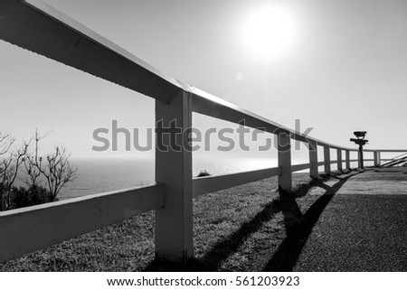 Black and white photo of a railing by the sea, Byron Bay Australia #561203923