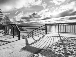 Black and white photo of a snow-covered fence and a descent to the beach on the winter embankment in the morning.